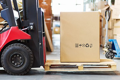 A forklift moving a box on a pallet